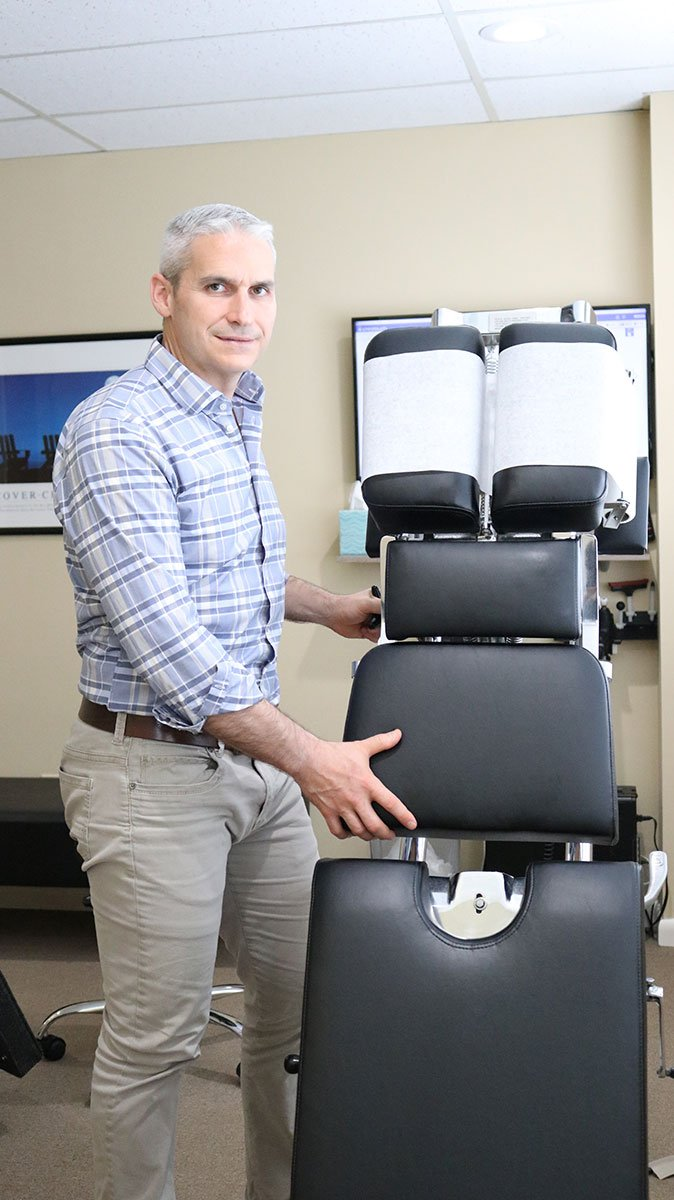Doctor Anthony Noya standing over a massage chair